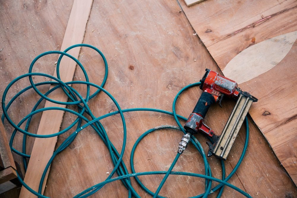 Nail gun tool with wood background in workshop.