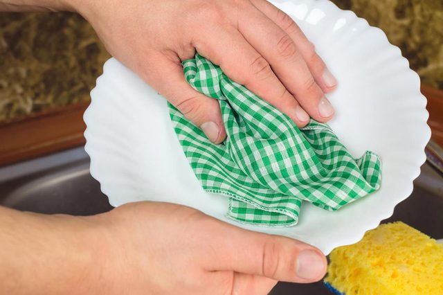 Man hands wipe with towel clean white dish at the kitchen