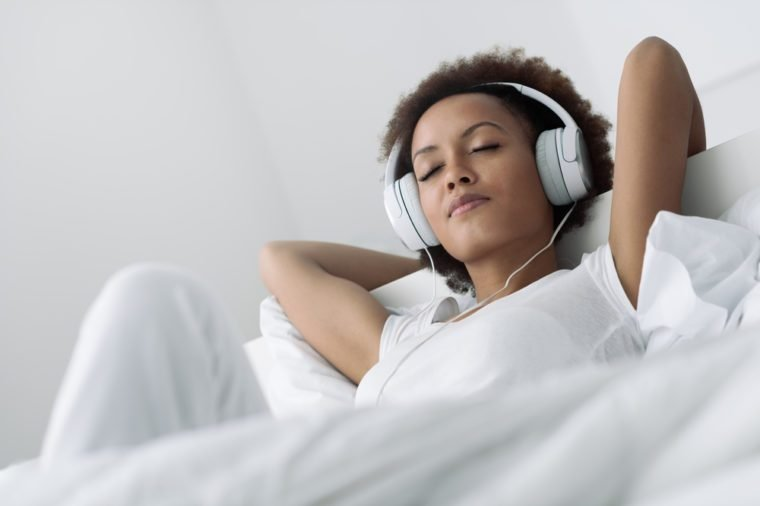 Young beautiful african american woman relaxing and listening to music using headphones, she is lying in bed