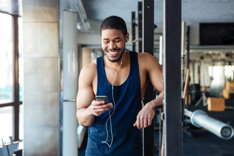 Healthy fitness man using smartphone in the gym, texting message