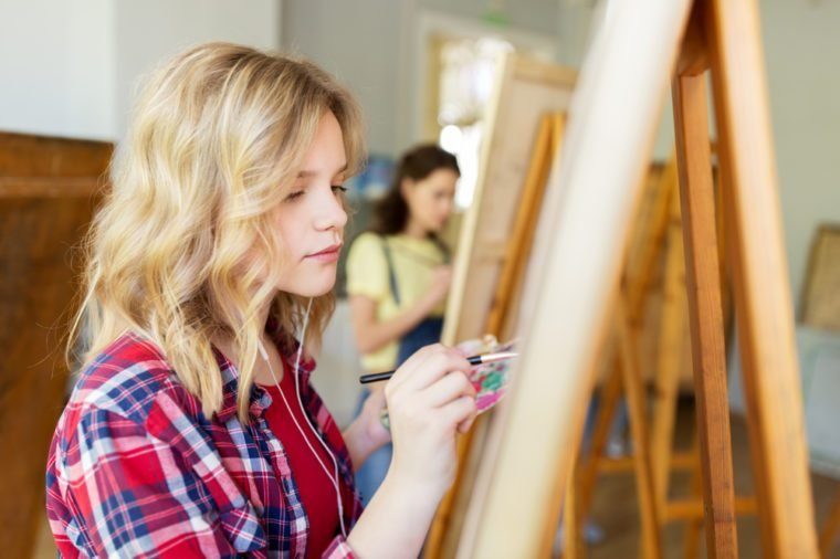 art school, creativity and people concept - student girl or artist with earphones, easel and paint brush painting at studio