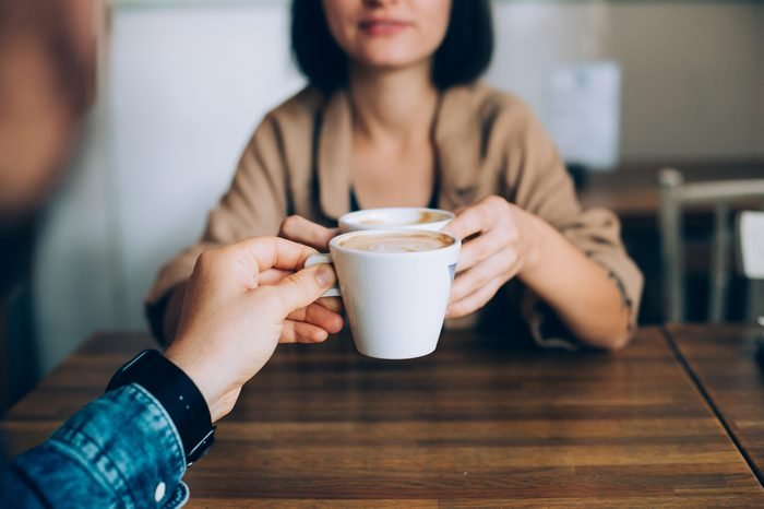 Man proposes gives coffee in white little cup to his girlfriend or partner, they are in love and are on romantic date in downtown stylish cafe or restaurant, drink artisan specialty