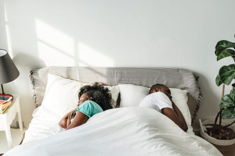 Black couple sleep together back to back