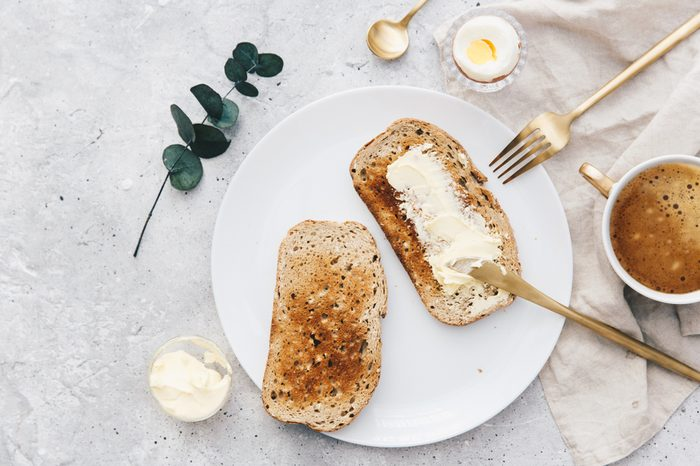 Flat Lay Slice of white buttered toast on a plate. Breakfast concept