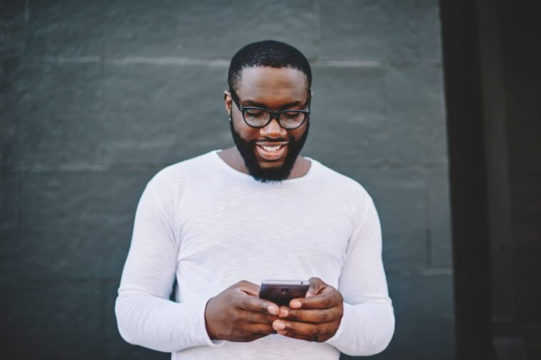 Cheerful african american man in spectacles searching cafes and restaurants in application on mobile,smiling dark-skinned guy reading news from networks on phone standing on copy space for advertising