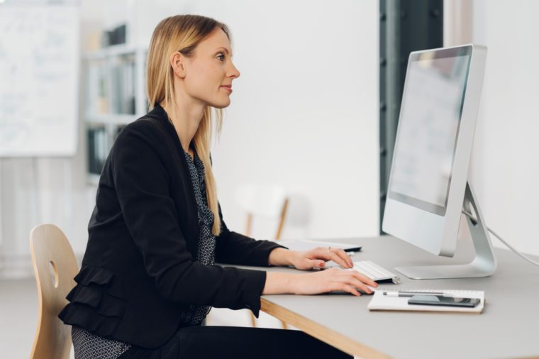 Side view of a beautiful woman sitting at desk while working on a modern desktop computer in the office
