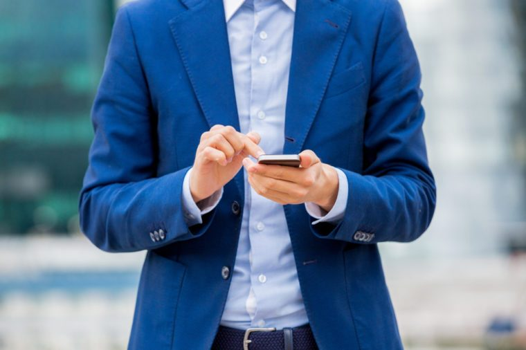 Handsome businessman in suit standing at the street with smart phone in hand. Modern skyscrapers on the background. Close-up