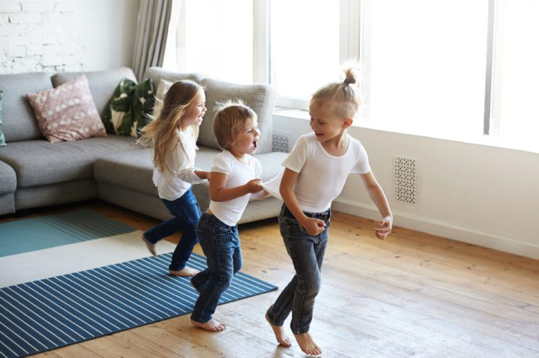 Action freeze shot of three happy joyful children one girl and two boys pullin each other by clothes while doing conga line, screaming in joy and excitement. Happiness, childhood and leisure