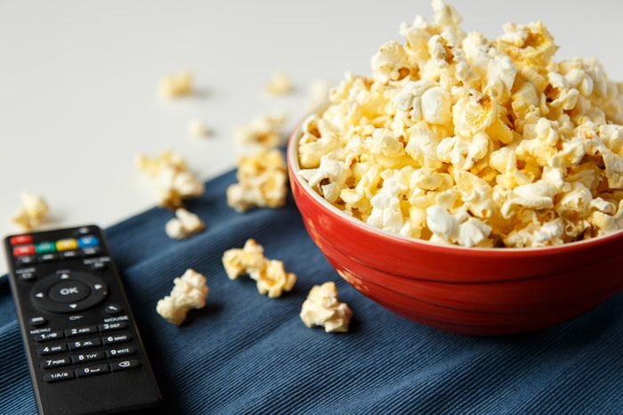 Popcorn in red bowl with tv remote on white table, selective focus.