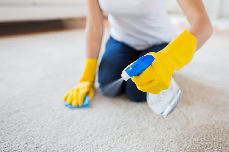 people, housework and housekeeping concept - close up of woman in rubber gloves with cloth and derergent spray cleaning carpet at home