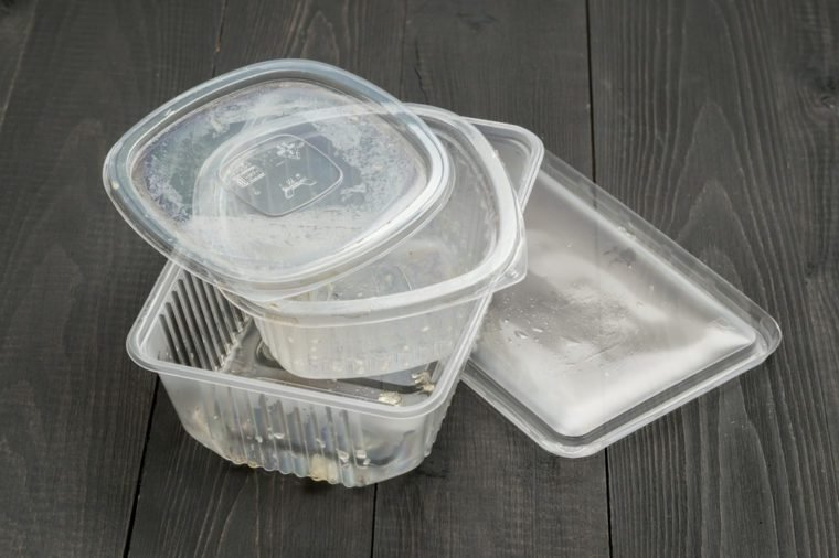 Dirty plastic food container on dark wooden background. Used food box as Garbage. Environmental pollution concept