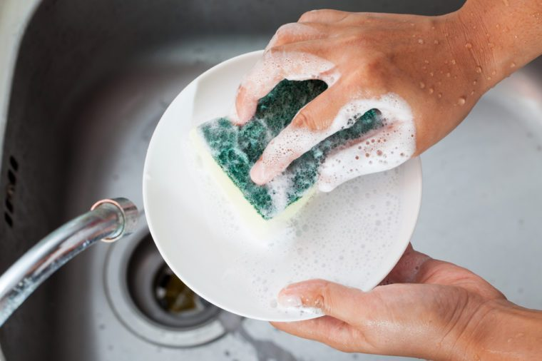 Woman hand washing dishes over the sink in the kitchen