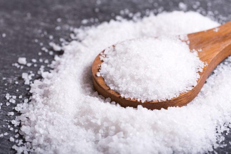 sea salt in a wooden spoon on dark table.