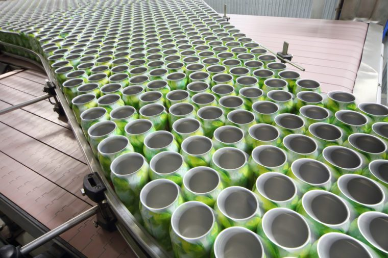 Many open green cans for drinks move on conveyor at large modern factory.
