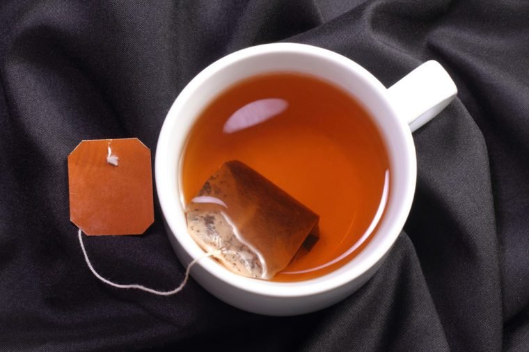A cup of tea with tea bag on a black simple background