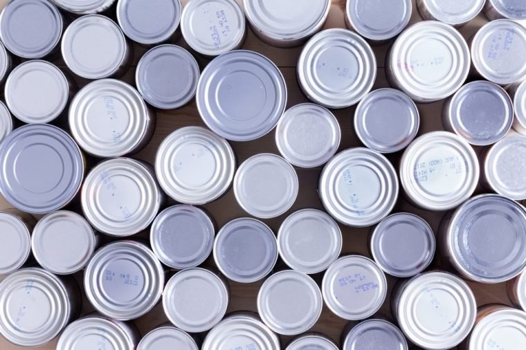 Background of multiple sealed food cans or tins viewed from overhead in an assortment of sizes filling the frame in a food and nutrition concept