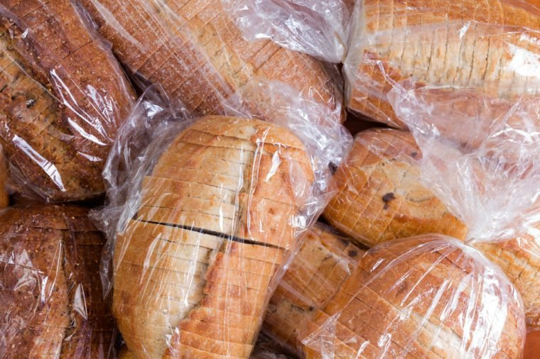 Plastic bags of assorted varieties of fresh sliced bread for a food drive piled on top of one another in a full frame background view