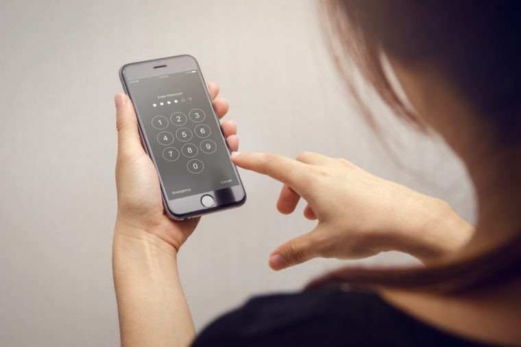 Close up woman hand holding smartphone while entering the passcode.