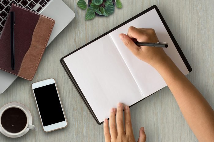 Woman hands writing on book in office.Business woman working on desk of wood.Business woman working with laptop and office supplies on top view.Copy space.