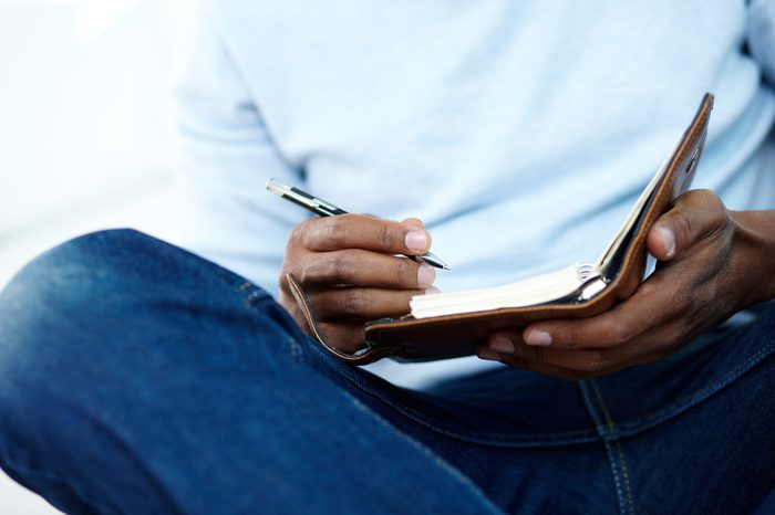 Hands of young African man writing something in notepad