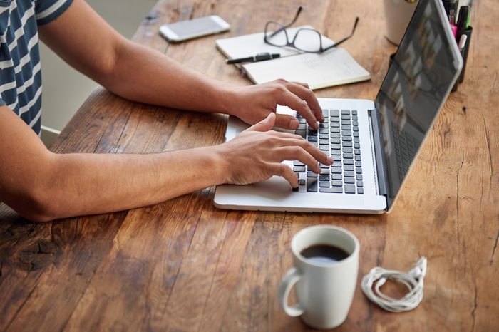 Cropped shot of a man's hands typing on a laptop that is on a wooden desk with a mug of coffee alongside