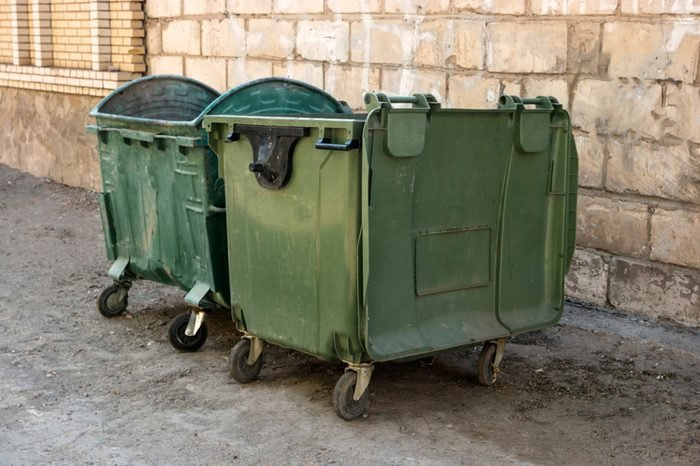 Two Green Trash Dumpsters In Front Of White Brick Wall Angle View in ghetto.