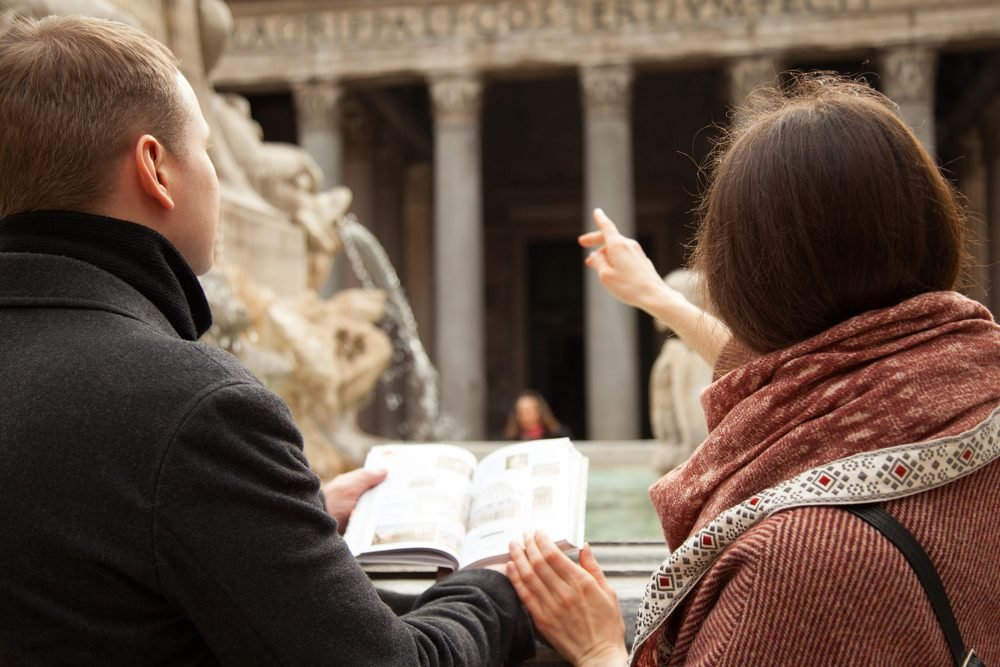 Unrecognizable young couple of travelers looking at Pantheon and holding touristic guide