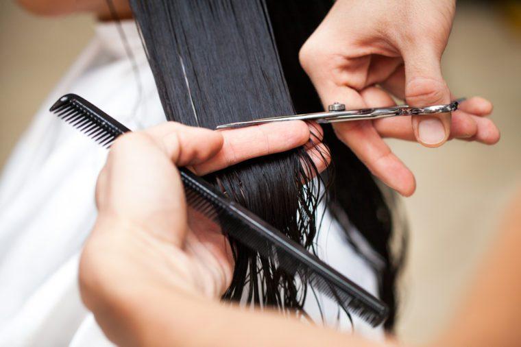 Hairdresser's hands cutting hair.