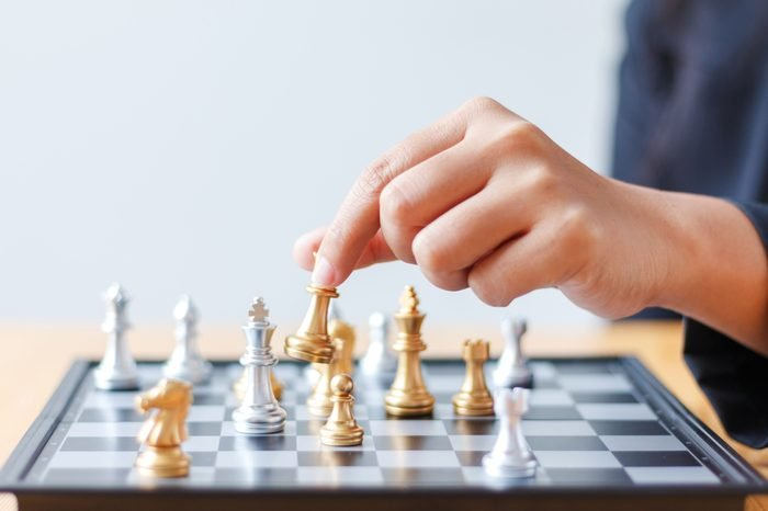 Close up shot hand of business woman moving golden chess to defeat a silver king chess on white and black chess board for business challenge competition winner and loser concept, selective