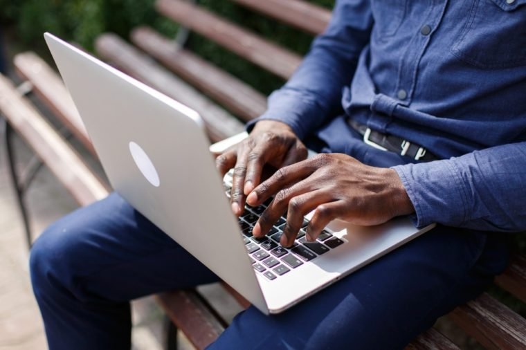 Hands of African American man typing something on the laptop while he sits on the bench outside