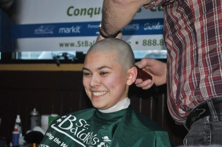 Alaska state House page Hanna Davis smiles as she gets her head shaved at a fund-raiser for St. Baldrick's Foundation, in Juneau, Alaska. Davis was among a number of state legislators, pages and community members who got their heads shaved for the childhood cancer research charity