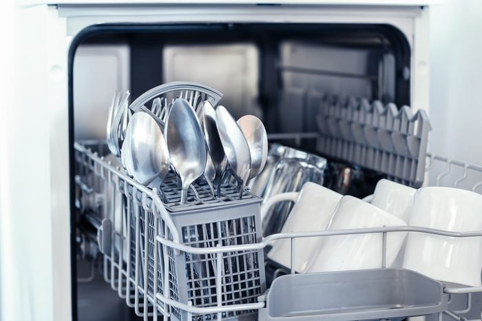 An open dishwasher with clean dishes in a white kitchen, front view.utensils, selective focus.Dishwasher with clean white dishes.