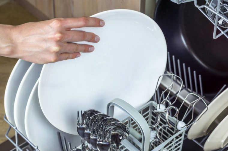 Unloading clean dishes from the dishwasher machine. Focus on hands.