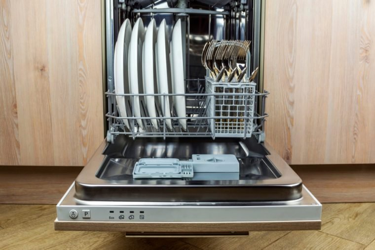 Dishwasher with clean cutlery and plates