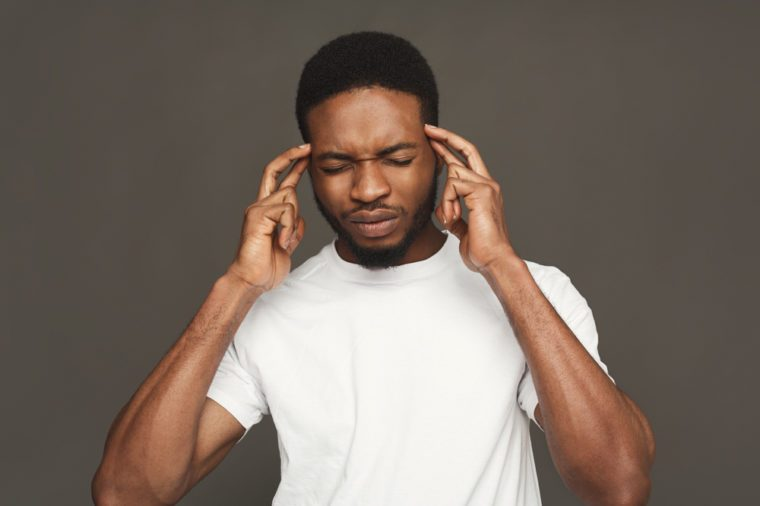 Headache. Concentrated pensive black man thinking about something, holding fingers on temple, white studio background