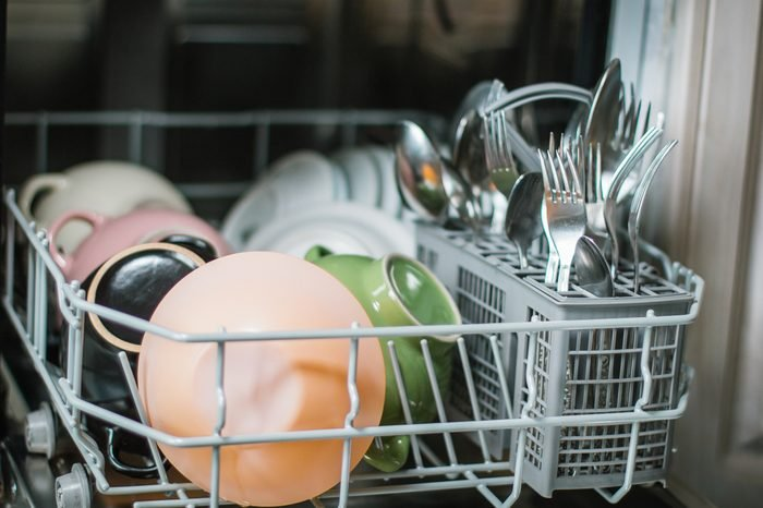 Open dishwasher with clean glass and dishes, selective focus, Clean after washing in the dishwasher. bright colorful dishes.