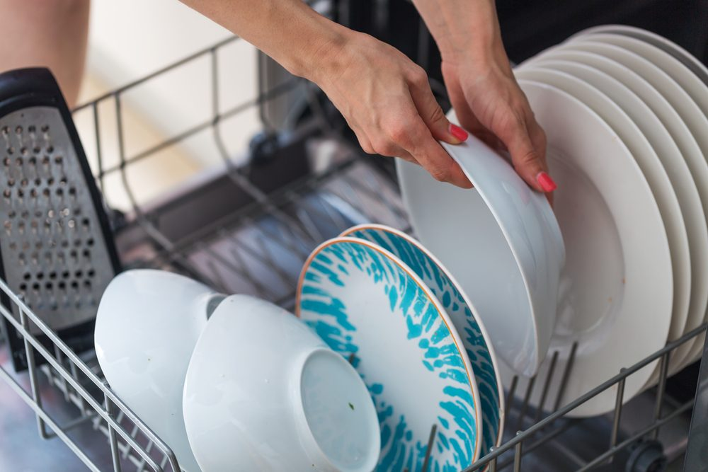 Woman's hand putting a white plate into the dishwasher; a household chore