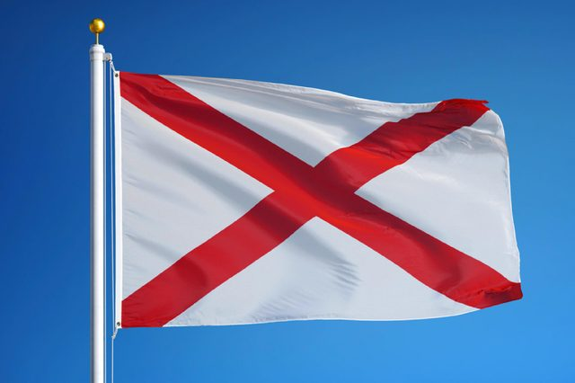 Alabama (U.S. state) flag waving against clear blue sky, close up, isolated with clipping path mask alpha channel transparency, perfect for film, news, composition