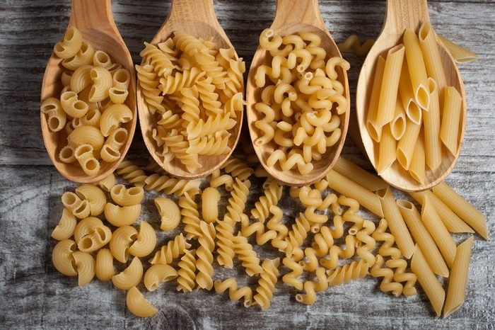 Various mix of pasta on wooden rustic background, sack and wooden spoons. Diet and food concept.