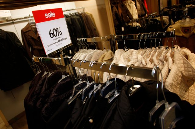A discount sign stands on top of a rack of coats on sale at a Macy's department store