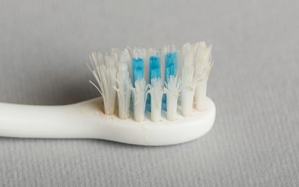 Old used toothbrush on grey background. Close-up