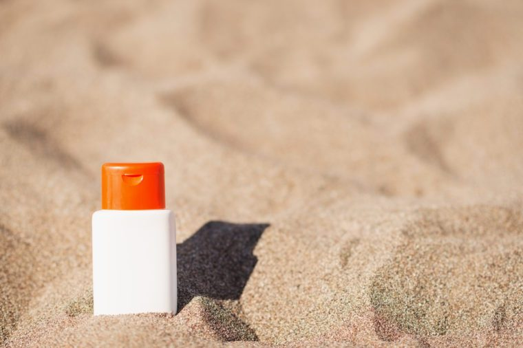 Bottle of sun block creme on sand