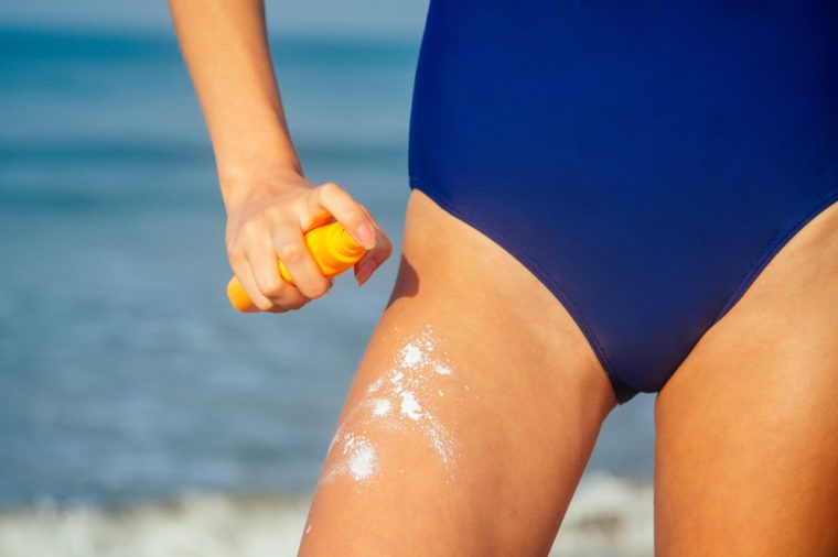 a woman is applying sunscreen on her thighs