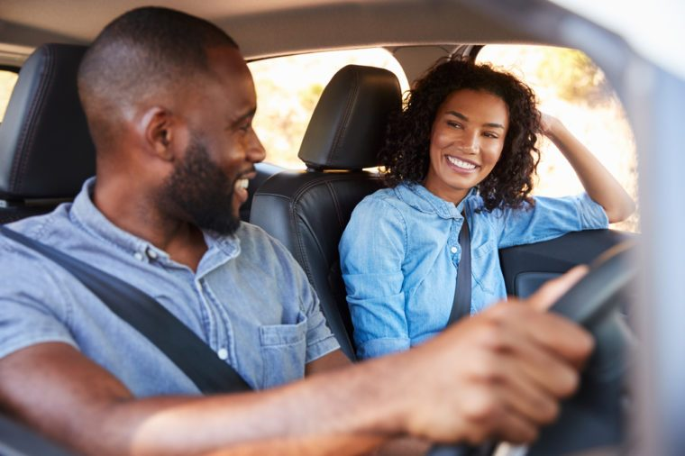 Young black couple in car on road trip smiling at each other