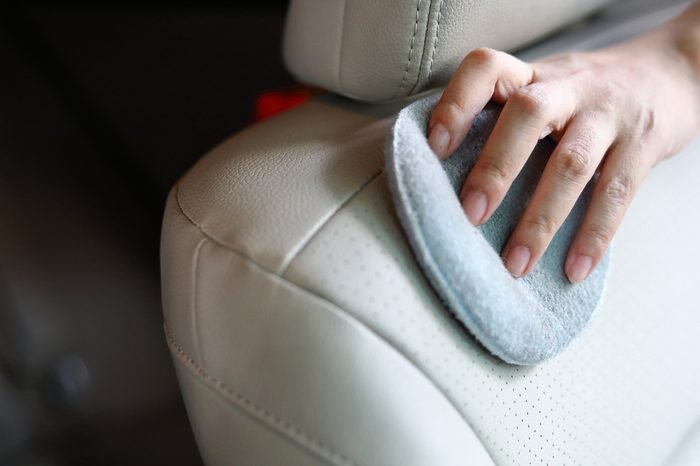woman hand cleaning leather seat with soft fabric sponge waxing polished, car wash