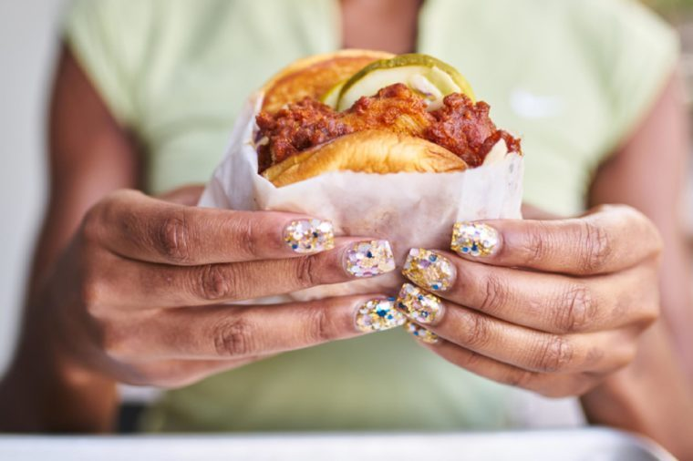 close up of woman with pretty nails holding fried spicy chicken sandwich
