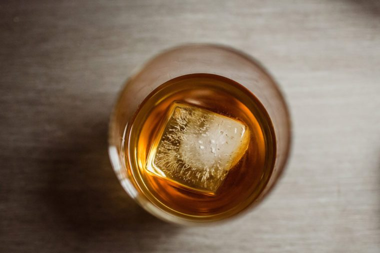 whiskey glass with ice cube from above