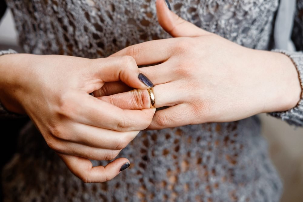 woman takes off an engagement ring, family conflict, close-up