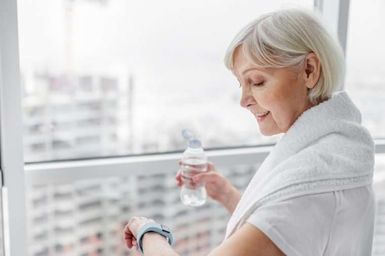 Senior woman using smartwatch after training