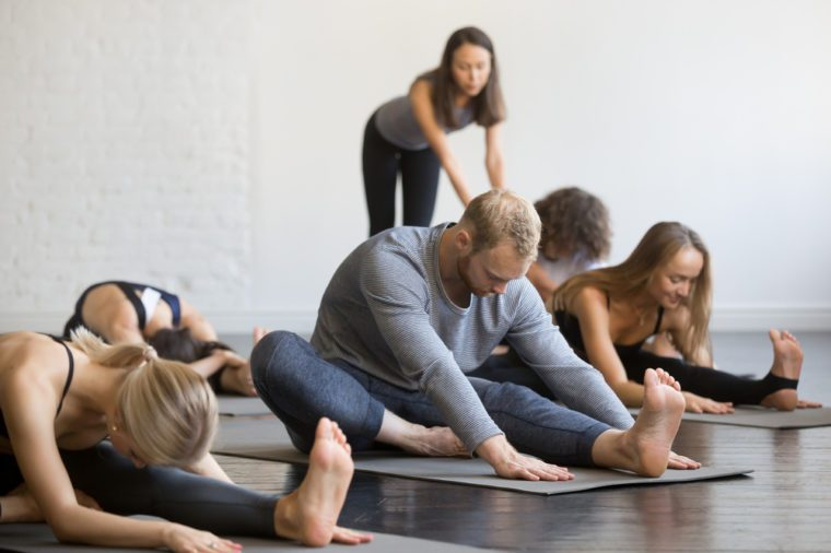 Group of young sporty people practicing yoga lesson with instructor, sitting in Janu Sirsasana exercise, Head to Knee Forward Bend pose, working out, indoor, studio. Wellbeing, wellness concept